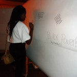 Sankofa Scholar, Toshe, writes on the message wall at the 2014 Blacktivism Conference